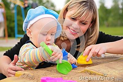 Het spel van de moeder en van het kind in zandbak