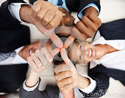 Het team van bedrijfsmensen die duimen tonen ondertekent omhoog