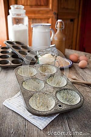 Het tin van de muffin beboterd met maïsmeel