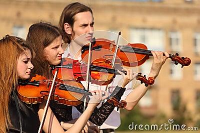Het trio van violisten speelt openlucht