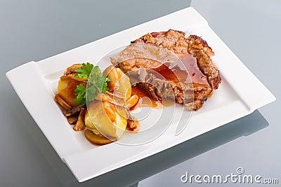 Het varkensvlees van het braadstuk met jus en aardappels