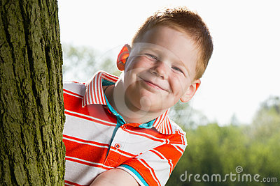 Het verbergen van de jongen achter boom