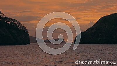 Het vestigen van schot van een eiland beslagen oceaan bij zonsondergang stock video