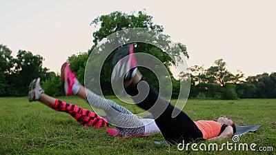Het voelen van uw abs meisjes Groep jonge atletische mensen in sportkleding die lichaamsbewegingen op groen gras in de zomer doen stock videobeelden