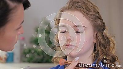 Het voorbereiden van de huid van het model voor het toepassen van make-up Het verwerken van het gezicht met een borstel met een t stock footage