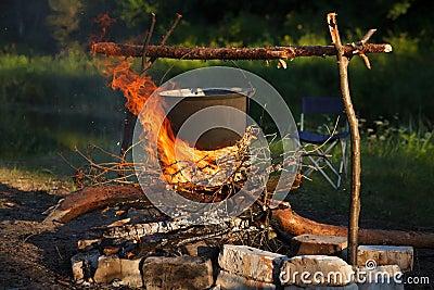 Het voorbereiden van voedsel in grote pot op kampvuur