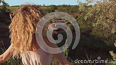 Het vrolijke en blije meisje met blond krullend haar spint op zijn plaats, haar krullendaling op haar gezicht, glimlacht oprecht  stock videobeelden