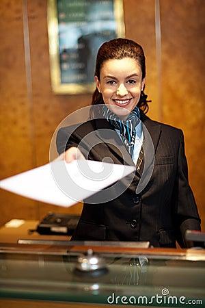 Het vrolijke vrouwelijke receptionnist aanbieden