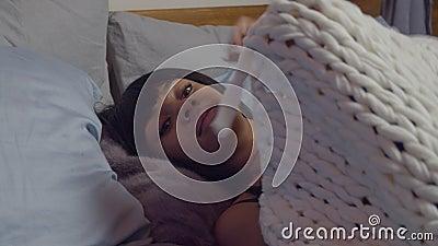 Het vrouwtje stilzetten onder een warme deken in bed stock footage