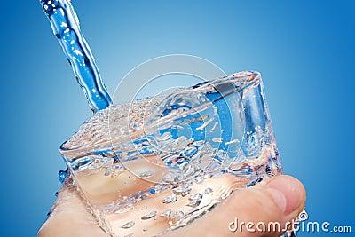 Het water wordt gegoten in een glas