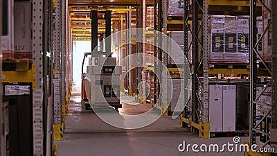 Het werk forklifts in het pakhuis Vorkheftruck met dozenritten tussen de rijen in het pakhuis Industrieel binnenland stock video