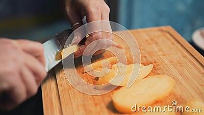 Het werk kookt close-up De chef-kok snijdt de aardappels cooking stock videobeelden