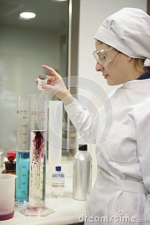 Het werkende laboratorium van de vrouw, de vaas van de glascilinder