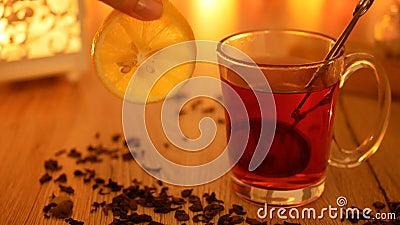 Hete aromatische thee in een kop met een hand die een citroen houden looping stock footage