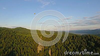 Hete Luchtballon die over de hemel in bergenlandschap vliegen stock video