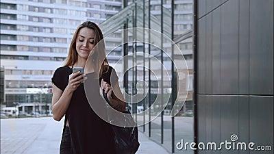 Heureux et dans des promenades de fille d'amour par la ville avec un téléphone banque de vidéos
