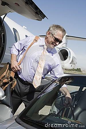 Hög affärsmanKeeping Luggage In bil