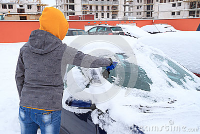 Hielo que raspa de la mujer de la ventanilla del coche