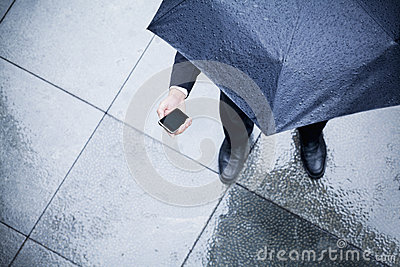 High angle view of businessman holding an umbrella and looking at his phone in the rain