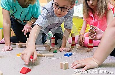 Female educator teaching children to build a train circuit durin Stock Photo