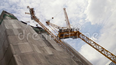 High Rise Building Construction. Low angle to the crane machines of a high rise building construction site stock footage
