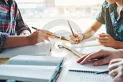 High school or college students studying and reading together in Stock Photo
