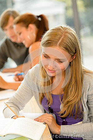 High-school student taking notes in library study