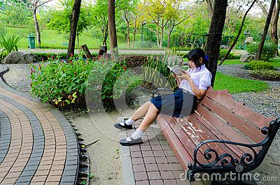 High-Schoolgirl reading in the park