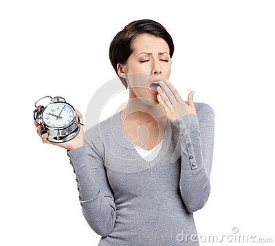 High time to sleep. Yawning woman and alarm clock