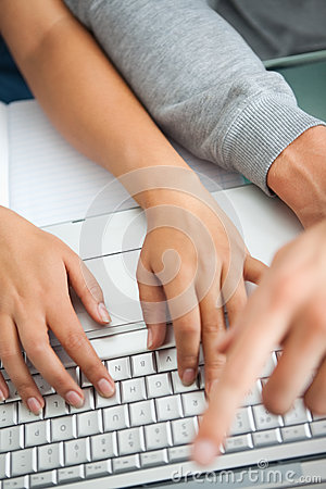 High view of students hands working with a laptop
