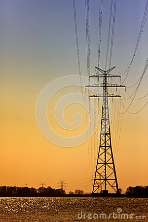 High voltage power line pylons at sunset