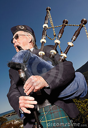 Highlander wearing kilt and playing bagpipes