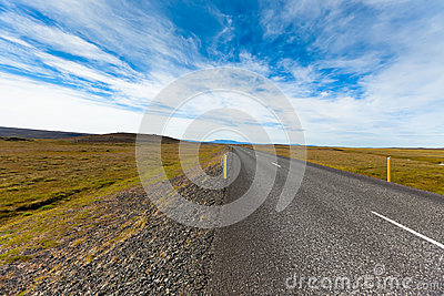 Highway through Icelandic landscape under a blue summer sky with