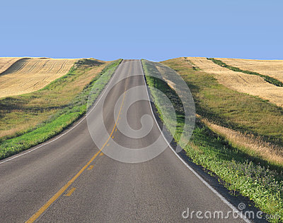 Highway through prairie wheat fields