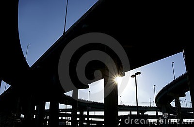 Highway ramps in silhouette with sun burst