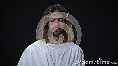 Hijo sufridor de los ojos de cierre de dios en el fondo oscuro, fe en el milagro, alcohol almacen de metraje de vídeo