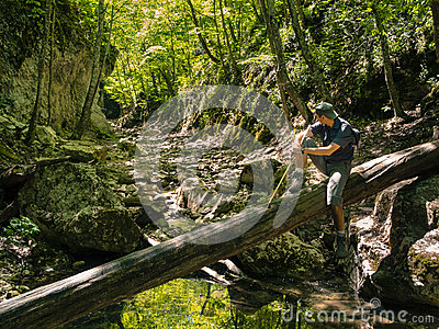 Hiker in the canyon of mountain river