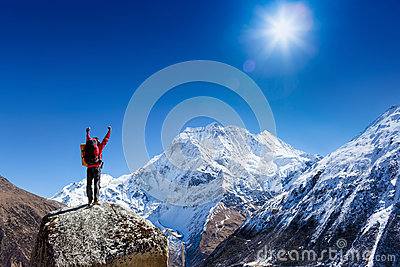 Hiker cheering elated and blissful with arms raised in the sky after hiking to mountain top summit Stock Photo