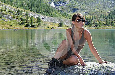 Hiker girl poses by an alpine lake