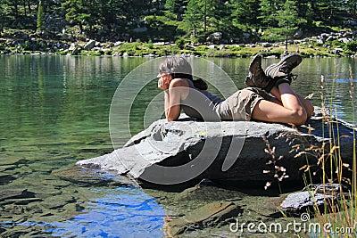 Hiker girl on a stone staring at lake
