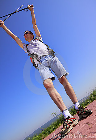Hiker with raised arms and trekking sticks