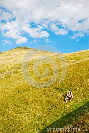 Hiker resting on mountain slope