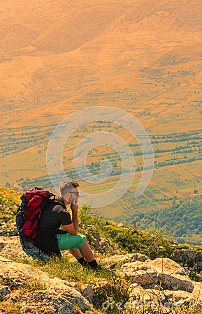Hiker Resting on Rocks in Mountains