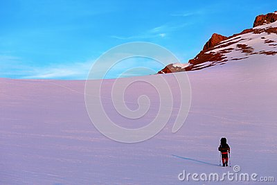 Hiker in sunrise snow mountains