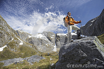 Hiker On Top Of Boulder In Mountains