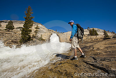 Hiker treking along cascades.