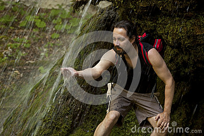Hiker under a waterfall