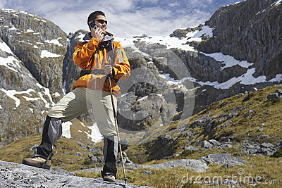 Hiker Using Cellphone With Walking Stick In Mountains