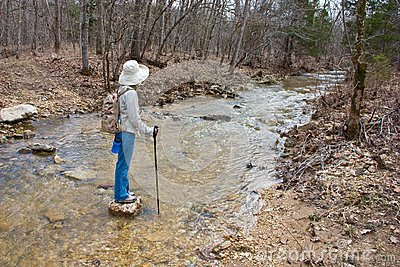 Hiker walking across a stream.