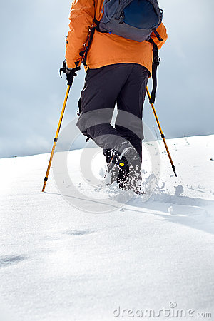 Hiker walking up on a snow-covered slope